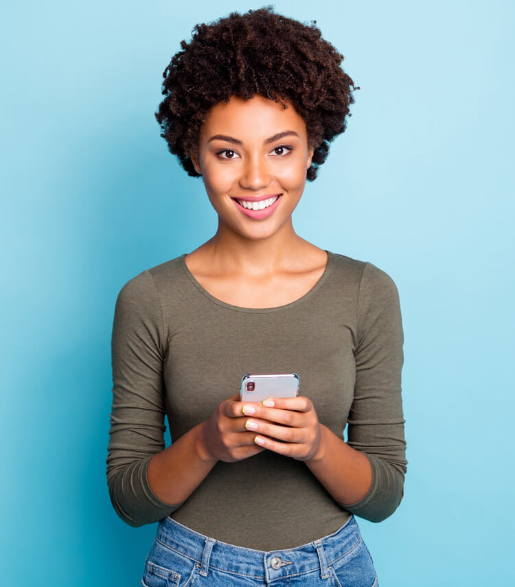 Portrait of a young woman holding her phone and smiling