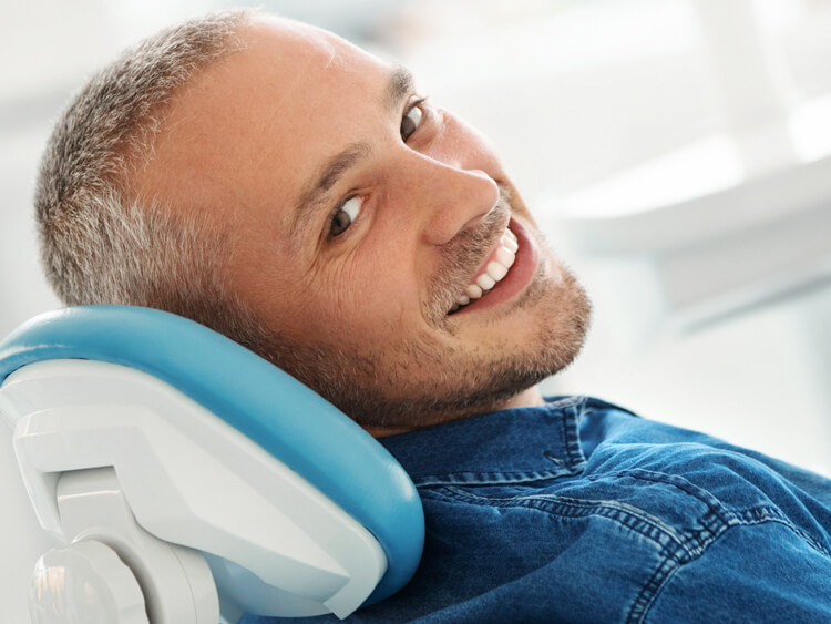 A middle-aged man reclining in a dental chair