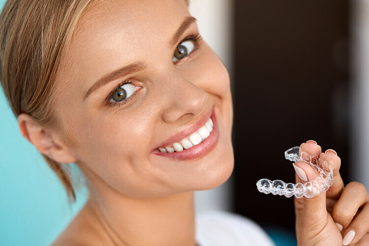 A young woman holding her Invisalign clear aligners