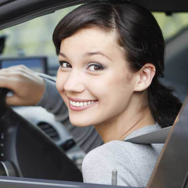 A young woman looking back and smiling while driving a car